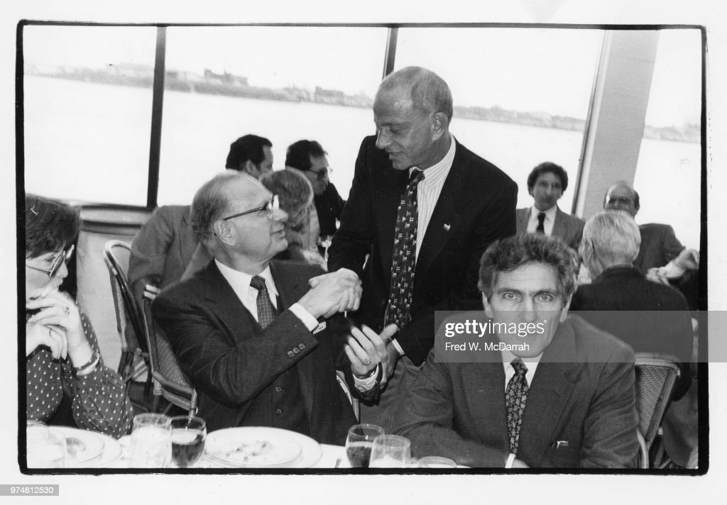 American politician and leader of the Kings County Democratic Party Meade Esposito (1907 - 1993) (seated center) shakes hands with attorney Roy Cohn (1927 - 1986) during a Citymeals-on-Wheels Restaurant Week benefit at the Water Club (at 500 East 30th Street), New York, New York, November 17, 1983. The intensely staring man at right is unidentified.