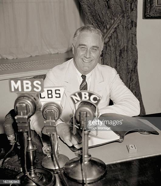 American politician and US President Franklin D Roosevelt smiles as he delivers one of his 'Fireside Chat' radio broadcasts from the Oval Office of...