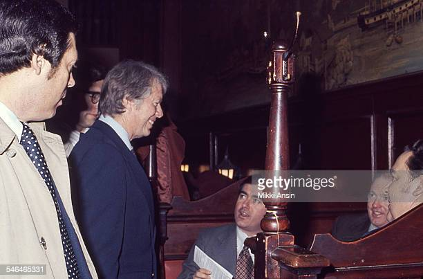 American politician and US Presidential candidate Jimmy Carter speaks with several men in a restaurant booth during his campaign Boston Massachusetts...