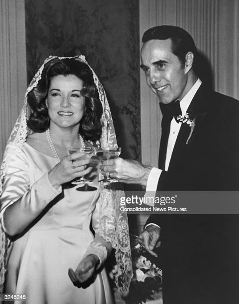 American politician Bob Dole and his bride Elizabeth Dole smile and toast their glasses of champagne on their wedding day She wears a lace veil