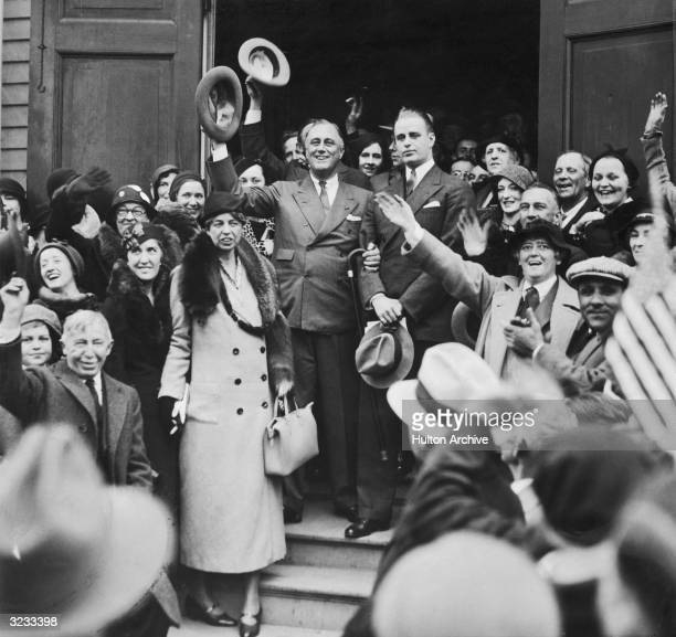 American politician Franklin D Roosevelt waves his hat in the air while being flanked by his wife social reformer Eleanor Roosevelt and their son...