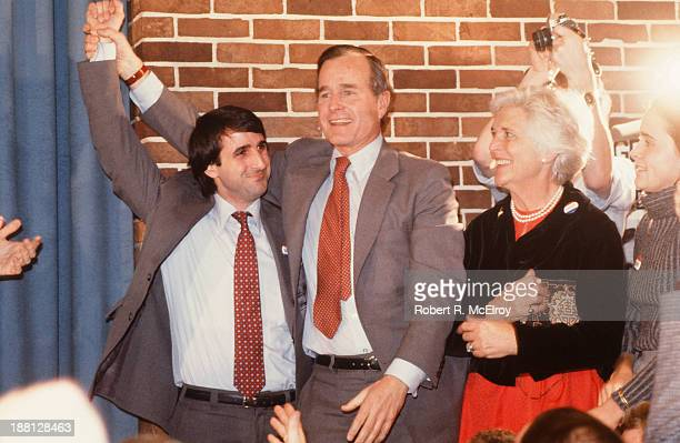 American politician George HW Bush and his wife, future First Lady Barbara Bush, celebrate with an unidentified man at an event during Bush's...