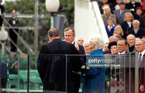 American politician George HW Bush takes the oath of office as he is swornin as 41st President of the United States by Chief Justice William...