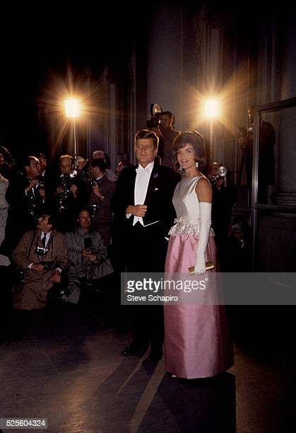 Jacqueline and John F Kennedy at a formal event with reporters