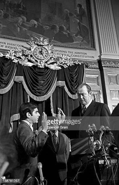 American politician MIchael Dukakis takes an oath as he sworn in as the 65th Governor of Massachusetts by State Senate President Kevin Harrington...