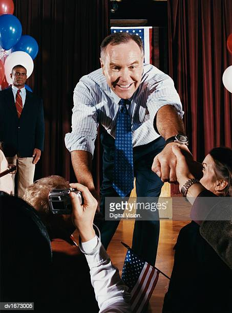 American Politician Reaching Out to Shake Hands with Supporters at a Political Rally