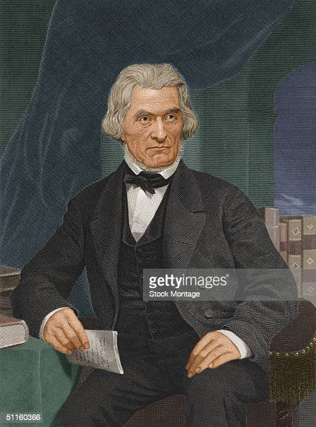 American politician Senator Secretary of State Secretary of War and Vice President John C Calhoun holds a document and sits by some books mid 19th...