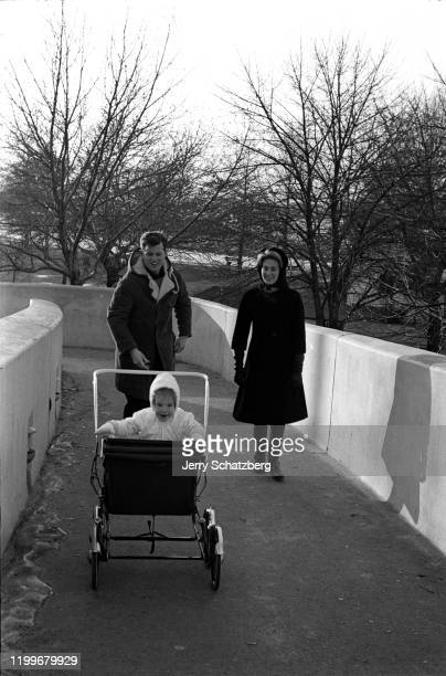 American politician Ted Kennedy and his wife Joan look at their daughter Kara bundled up in a stroller as they walk along a concrete pathway Boston...