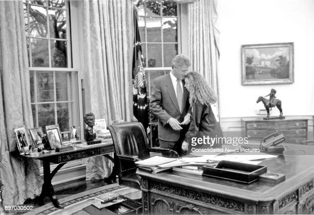 American politician US President Bill Clinton talk to his daughter, Chelsea, who leans against him in the White House's Oval Office, Washington DC,...