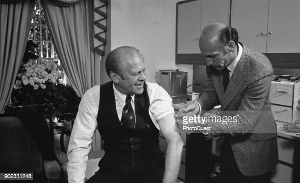 American politician US President Gerald Ford his sleeve rolled up is injected with a swine flu inoculation by White House physician Dr William Lukash...