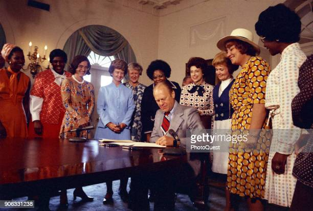 American politician US President Gerald Ford signs legislation declaring August 26th Women's Equality Day Washington DC August 22 1974 Also present...