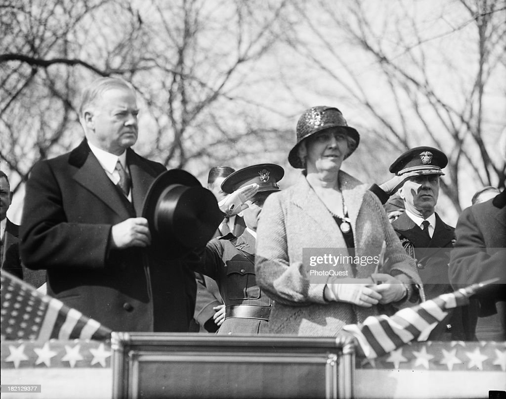 American politician US President Herbert Hoover (1874 - 1964) and his wife, First Lady Lou Henry Hoover (1874 - 1944), stand at attention on a reviewing stand, March or April 1932.