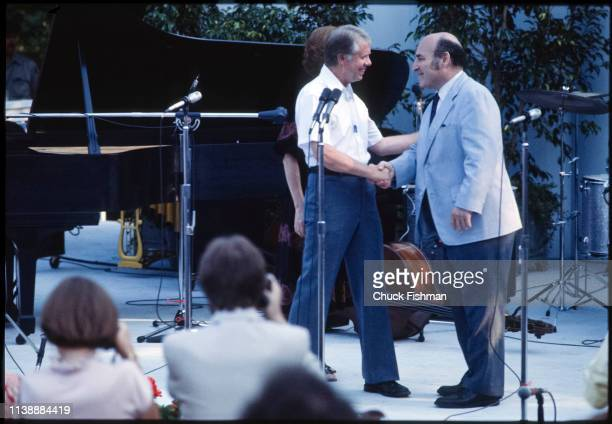 American politician US President Jimmy Carter shakes hands with Jazz promoter George Wein onstage during a White House Jazz concert on the South Lawn...