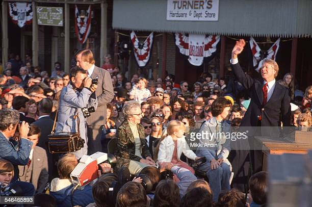 American politician US President Jimmy Carter stands his family seated behind him on a platform amid a crowd on W Main Street Plains Georgia January...