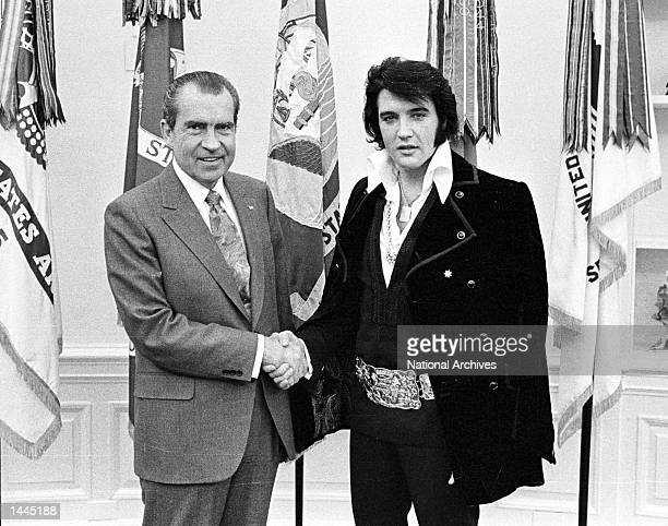 American politician US President Richard Nixon and Rock and Roll musician Elvis Presley shake hands during a meeting at the White House, Washington...