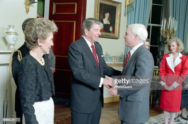 American politician US President Ronald Reagan shakes hands with Senator John McCain during a dinner for newly elected members of the 100th Congress...