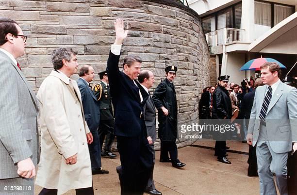American politician US President Ronald Reagan smiles and waves as he leaves the Washington Hilton Hotel, Washington DC, March 30, 1981. Among those...