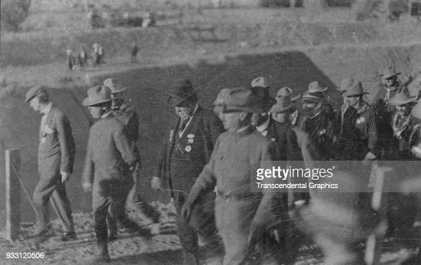 American politician US President William Howard Taft walks with dignitaries and law enforcement officers during the opening of the Gunnison...