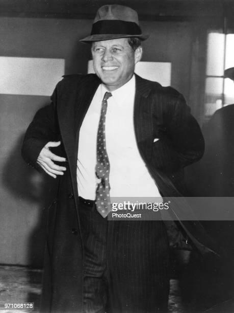 American politician US Senator John F Kennedy smiles as he puts on his overcoat Wisconsin Febraury 1960