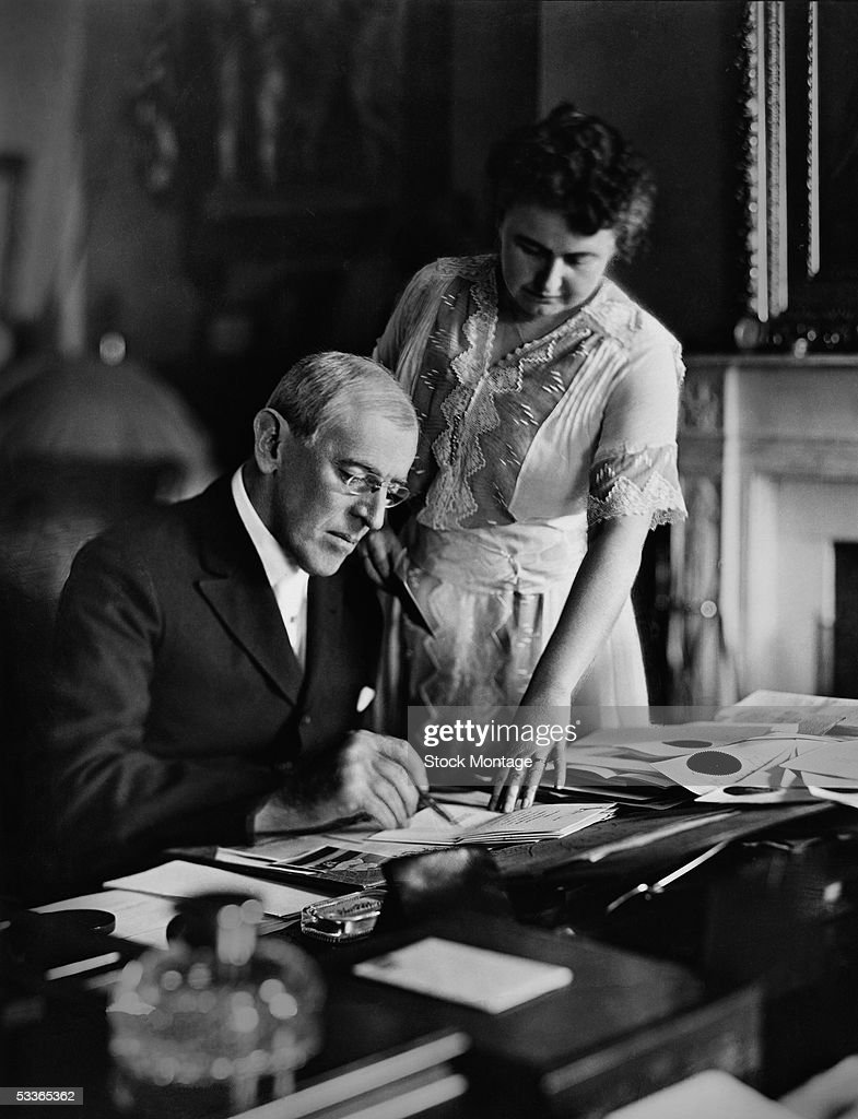 American politician Woodrow Wilson (1856 - 1924), President of the United States from 1913-1921, goes over papers at his desk as his second wife Edith Bolling Galt Wilson (1872 - 1961) looks on, mid 1910s. Edith was often referred to as 'secret president' because of the important role she played in Wilson's presidency during his long and debilitating illness following a stroke.