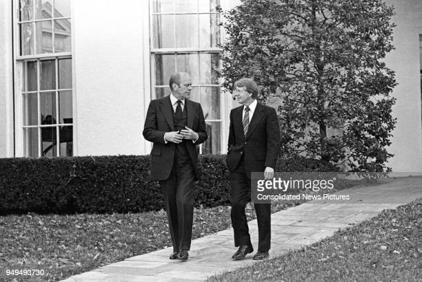 American politicians US President Gerald Ford and US President-Elect Jimmy Carter as they walk together outside the White House, Washington DC,...