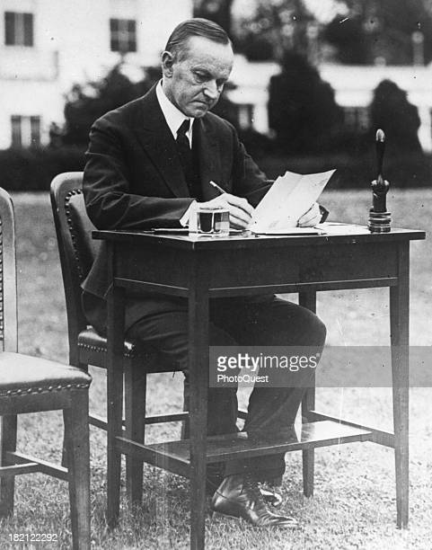 American poltician US President Calvin Coolidge sits at a writing desk on the White House lawn as casts his absentee ballot for the 1924 general...
