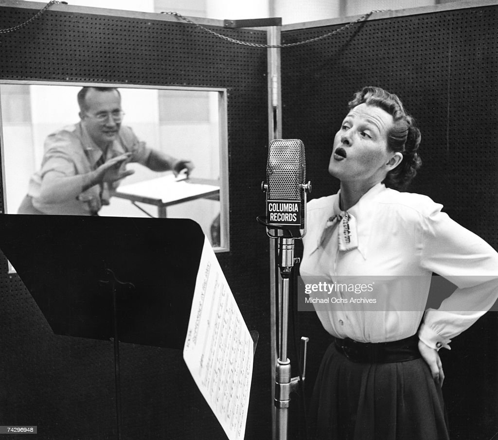 American pop and jazz singer Jo Stafford (1917-2008)sings into a mcrophone in a recording studio as her husband, arranger Paul Weston, conducts from the adjoining room. Photo by Michael Ochs Archives/Getty Images
