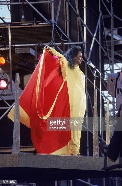 American pop and RB singer Diana Ross performs on stage in a yellow outfit holding a red cape behind her during her Central Park concert New York...