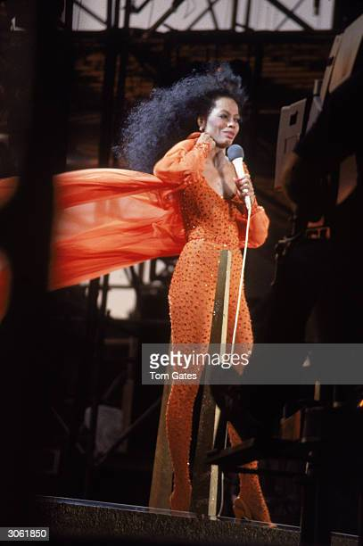American pop and RB singer Diana Ross performs on stage in her Central Park concert wearing an orange outfit with her cape blowing behind her New...