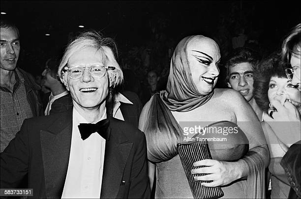 American Pop artist Andy Warhol and drag performer Divine arrive at the reopening party at the Copacabana nightclub held in Warhol's honor New York...