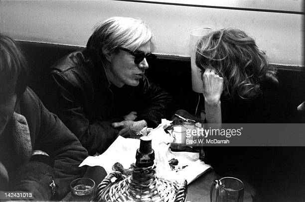 American pop artist Andy Warhol and others sit at a table in Max's Kansas City New York New York December 19 1966