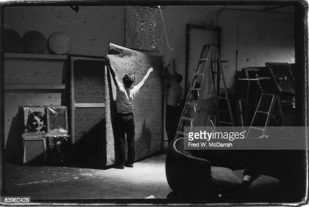 American pop artist Andy Warhol and poet Gerard Malanga attach a canvas to a frame in the Factory Warhol's studio New York New York September 5 1964...