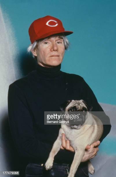 American pop artist Andy Warhol holding a pug 1982