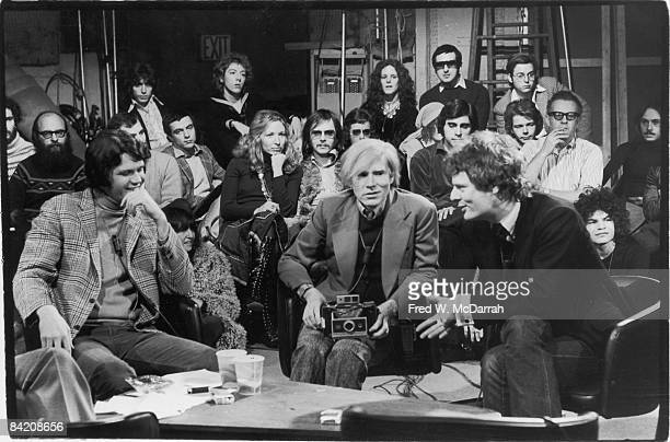 American pop artist Andy Warhol holds a camera as he listens to film director Paul Morrissey answer a quesion while author and television host Dotson...