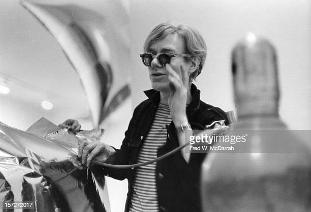 American pop artist Andy Warhol inflates his 'Silver Clouds' installation at the Leo Castelli Gallery New York New York April 1 1966 The mylar...