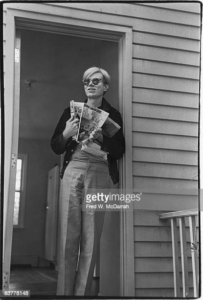 American pop artist Andy Warhol leans against a door frame and holds an open copy of Hullabaloo magazine dated November 1966 Along with members of...