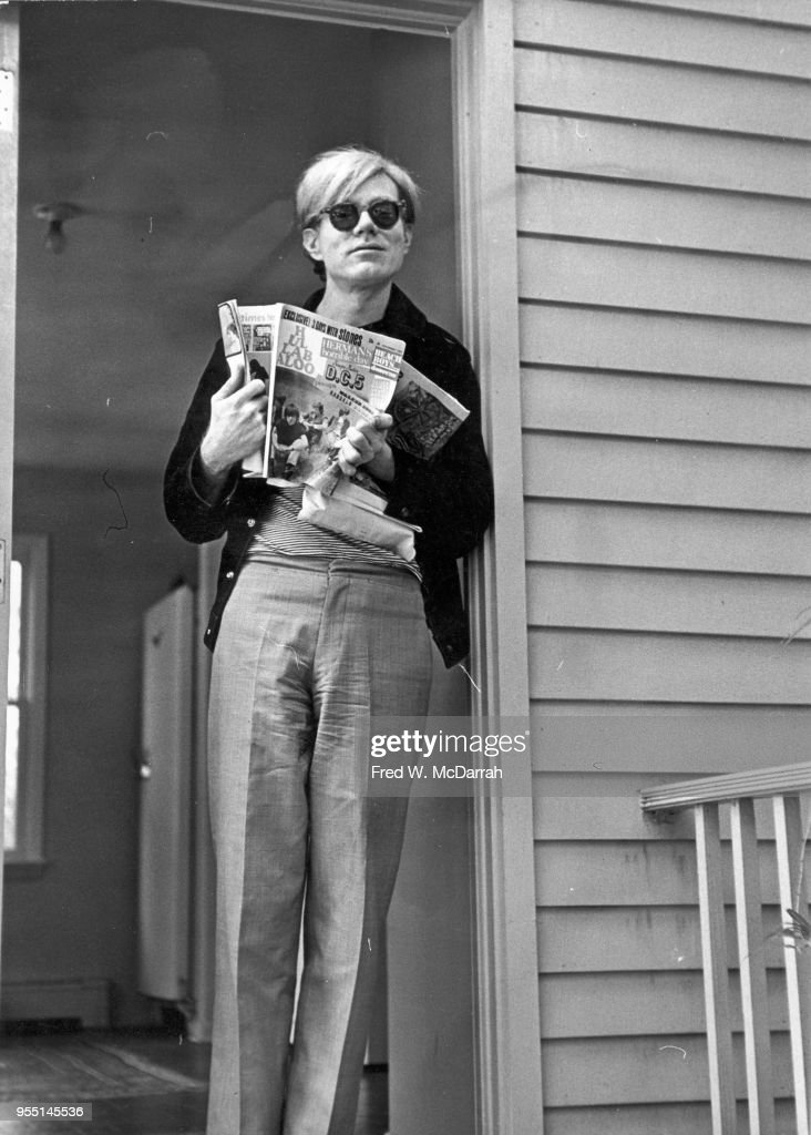 American pop artist Andy Warhol (1928 - 1987) leans against a door frame in Stan Vanderbeek's studio, Stony Point, New York, September 22, 1966. Heholds an open copy of Hullabaloo magazine dated November 1966. He was at the studio as part of a 'field trip' with members of the New York Film Festival.