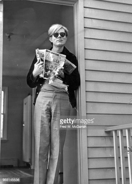 American pop artist Andy Warhol leans against a door frame in Stan Vanderbeek's studio Stony Point New York September 22 1966 Heholds an open copy of...