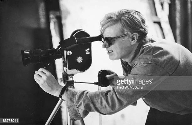 American pop artist Andy Warhol lines up a shot through the viewfinder of a 16mm Bolex camera during the filming of 'Taylor Mead's Ass' at his studio...