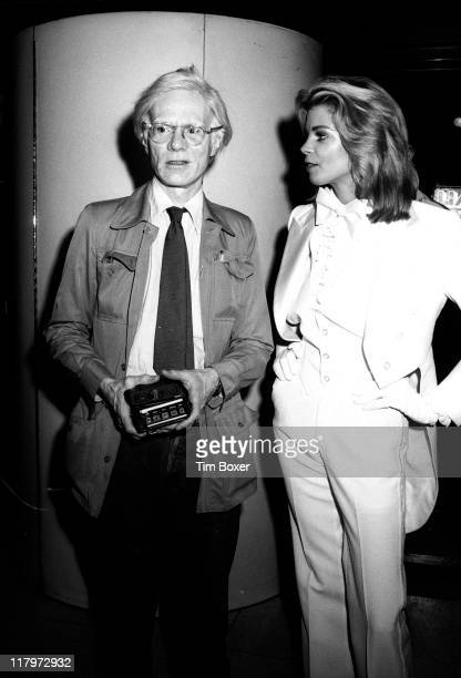American Pop artist Andy Warhol stands with actress and former Playboy cover girl Kristine DeBell dressed in a white tuxedo at the premiere of her...