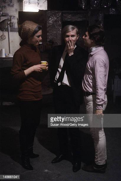 American pop artist Andy Warhol stands with model and actress Edie Sedgwick and poet Gerard Malanga in the Factory Warhol's studio New York New York...