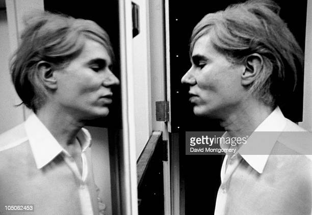 American pop artist Andy Warhol studies his reflection in a mirror circa 1966