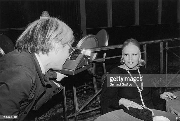 American pop artist Andy Warhol uses a Polaroid camera to photograph singer singer Peggy Lee at an unidentified event early 1970s