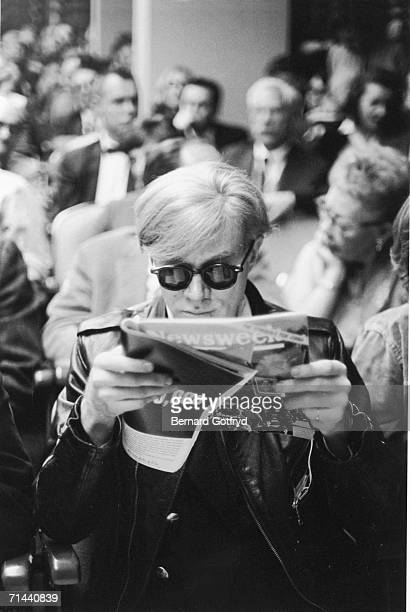 American pop artist Andy Warhol wearing sunglasses and a leather jacket sits amongst others in an audience and reads a copy of Newsweek magazine New...