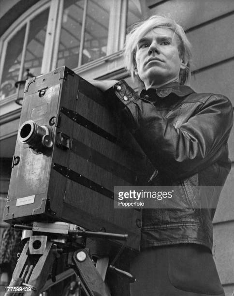 American pop artist Andy Warhol with a vintage plate camera on a tripod, circa 1965.