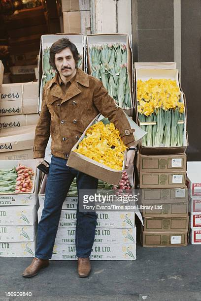 American pop artist Ed Ruscha holding a box of daffodils outside a florist's shop, circa 1970.