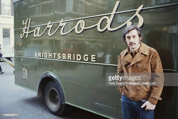 American pop artist Ed Ruscha standing in front of a Harrods van, circa 1970.