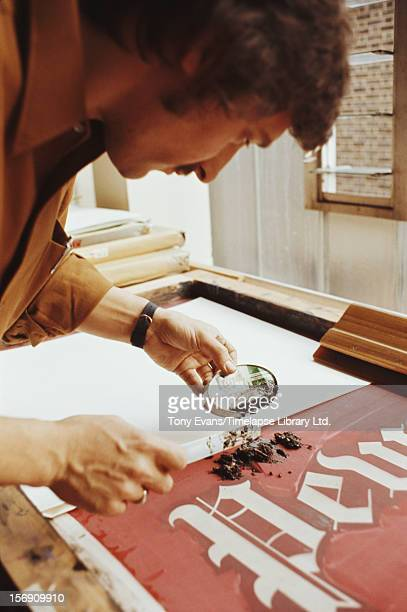 American pop artist Ed Ruscha working on his mixed-media lithograph 'Pews', circa 1970.