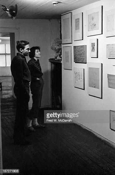 American Pop artist Robert Rauschenberg and Gloria McDarrah look art works on the wall of Rauschenberg's Front Street loft studio New York New York...