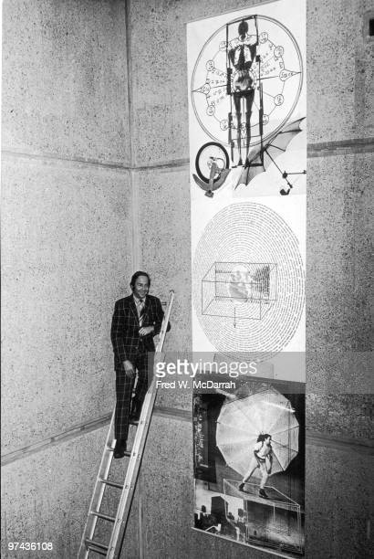 American Pop artist Robert Rauschenberg poses at the top of a ladder next to a massive bannerlike work at the Whitney Museum of American Art New York...